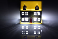 Two houses at night, one has lights on. With a dark background stock images