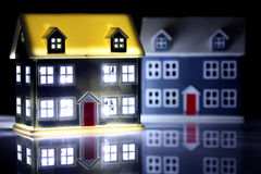 Two houses at night, one has lights on. Against a black background royalty free stock photography