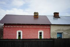 Two houses. red brick vs grey. Somewhere in Romania, seen from the train, one new house grey color has been added to an old house wich has been remodeled. The stock photography