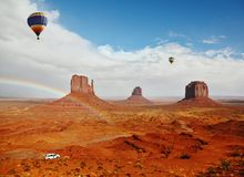 Two huge balloons flies over Red Desert. The picturesque rainbow crosses some rocks - mitts. Two huge balloons flies over Red Desert Navajo, USA. On the road is stock photography