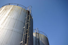 Two huge industrial silos against a blue sky Royalty Free Stock Images