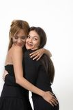 Two hugging ladies. In black dress. White background Royalty Free Stock Photo