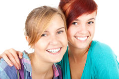 Two hugging teenage girls, friends. White background Royalty Free Stock Image