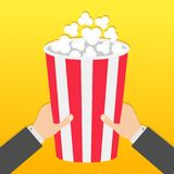 Two human businessman hands holding big popcorn box. Movie Cinema icon in flat design style. Pop corn. Fast food. Yellow gradient. Background. Vector Stock Photography