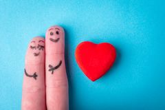 Two human fingers with heart on blue background. A happy couple in love with painted smiley and hugging.  royalty free stock photos