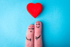 Two human fingers with heart on blue background. A happy couple in love with painted smiley and hugging.  stock images