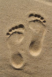 Two human footprints. Two well-shaped human footprints in the sand Stock Photo