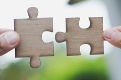 Two human hands connected jigsaw puzzle white, Joint Business Co. Ncepts royalty free stock photos