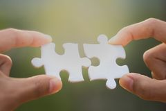 Two human hands connected jigsaw puzzle white, Joint Business Co stock image