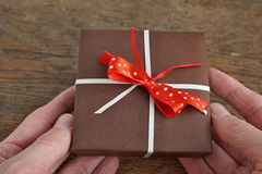 Two human palms holding a small brown gift box wrapped with white ribbon and red dotted bow on the wooden background Royalty Free Stock Images