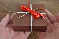 Two human palms holding a small brown gift box wrapped with white ribbon and red dotted bow on the wooden background Stock Image