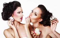 Two Hungry Women eating Pastries - Muffins and Cupcakes Stock Photography