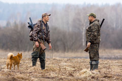 Two hunters and dog Royalty Free Stock Photo