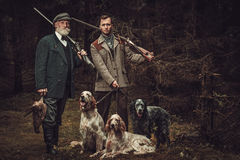 Two hunters with dogs and shotguns in a traditional shooting clothing, posing on a dark forest background. Stock Photography