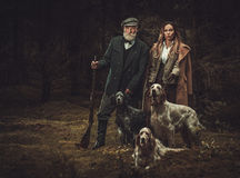 Two hunters with dogs and shotguns in a traditional shooting clothing, posing on a dark forest background. Royalty Free Stock Photos