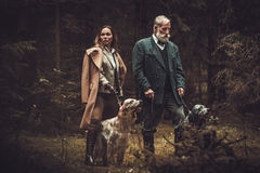 Two hunters with dogs and shotguns in a traditional shooting clothing, posing on a dark forest background. stock photo