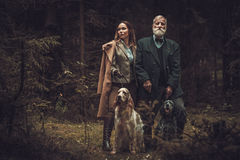 Two hunters with dogs and shotguns in a traditional shooting clothing, posing on a dark forest background. Royalty Free Stock Photo