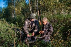 Free Two Hunters Father And Son Are Eating Together In The Forest. Bushcraft, Hunting And People Concept Stock Photography - 169120922