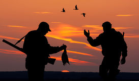 Two hunters at sunset Stock Photos