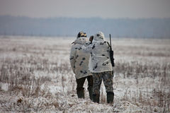 Two hunters in winter camouflage to sneak up on the field Stock Image