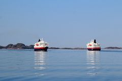 Two Hurtigruten  crossing. Two coastal steamer crossing in front of Bolga, Arctic Norway Royalty Free Stock Photography