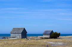 Two huts and a boat by the sea Stock Image