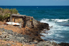 Two huts of palm leaves on the coastline of Crete near Malia Royalty Free Stock Photo