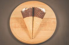 Two ice cream with cone in chocolate on a round wooden support/two ice cream with cone in chocolate on a round wooden support. Top stock photography