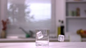 Two ice cubes falling in an empty glass Stock Image