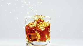 Two ice cubes falling into glass with brandy. Slow motion. Two ice cubes one by one falling into glass with brandy, when falling produces lot of splashing and stock footage