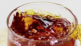 Two ice cubes falling into glass with whiskey. Slow motion. Two ice cubes one by one falling into glass with whiskey, when falling produces lot of splashing and stock video footage