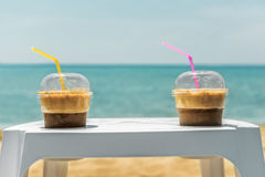 Two ice frappe coffee cups on beach. Two ice frappe coffee on white plastic coffee table in plastic transparent cups, with yellow and magenta straws, on summer Royalty Free Stock Photos