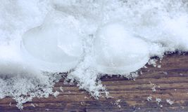 Two ice heart in snow on wooden plank, valentine`s day Stock Images
