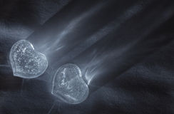 Two ice hearts with rays of light on textured background Stock Photo