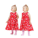 Two identical twin girls in red dresses looking Stock Photo