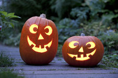 Two Illuminated Halloween pumkins in the garden Stock Images