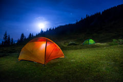 Two Illuminated orange and green camping tents. Under moon, stars at night stock photo