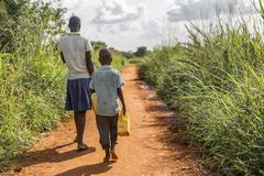 Two impoverished Ugandan kids carrying jerry cans on a walk to get water. stock photo