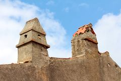Two improvised old chimneys made of concrete and parts of roof tiles on top of old house with dilapidated wall surrounded with. Cloudy blue sky on warm sunny stock photos