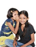 Two Indian kids gossiping with each other. Stock Photo