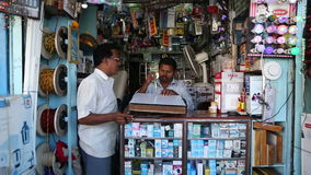 Two Indian man in a small street electronics shop. stock footage