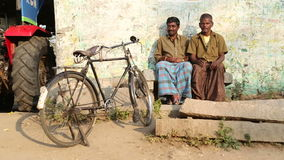 Two indian men sitting in front of house. HAMPI, INDIA - 28 JANUARY 2015: Two indian men sitting in front of house with bicycle standing alone stock footage