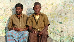 Two indian men sitting in front of house. HAMPI, INDIA - 28 JANUARY 2015: Portrait of two indian men sitting in front of house stock video