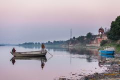 Two indian people float by the old wooden boat royalty free stock photos