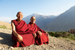 Two Indian tibetan monk lama. Two Indian tibetan old monks lama in red color clothing sitting in front of mountains Royalty Free Stock Photos