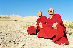 Two Indian tibetan monk lama. Two Indian tibetan old monks lama in red color clothing sitting in front of mountains Royalty Free Stock Photography