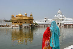 Two Indian women admire the Golden Temple, Amritsar. Located in the Punjab state of India Royalty Free Stock Images