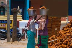 Two Indian women carry heavy bricks on their heads in traditional clothes. View from the back. Use of female labor at Stock Images