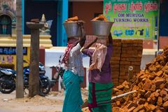 Two Indian women carry heavy bricks on their heads in traditional clothes. View from the back. Use of female labor at Royalty Free Stock Photos