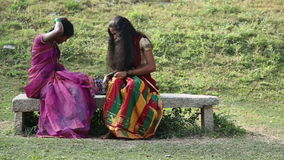 Two indian women sitting and combing their beautiful long dark hair. HAMPI, INDIA - 28 JANUARY 2015: Two indian women sitting and combing their beautiful long stock video